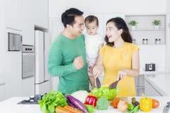 Genitori allegri e bambino che producono insalata fotografia stock