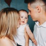 Genitori amorosi che abbracciano e che baciano la figlia del bambino fotografie stock libere da diritti