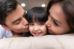 Genitori asiatici che baciano la loro poca figlia su entrambe le guance fotografie stock