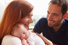 Genitori a casa con la figlia addormentata del neonato Immagini Stock Libere da Diritti