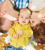 Genitori che abbracciano e che baciano bambino Fotografie Stock