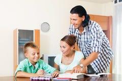 Genitori che aiutano con il compito Immagine Stock