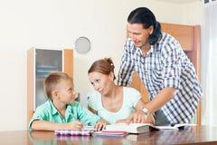 Genitori che aiutano a teenager con compito Immagini Stock