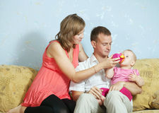 Genitori che alimentano il suo bambino con la bottiglia Fotografie Stock