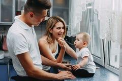 Genitori che alimentano la loro figlia adorabile con il cucchiaio immagine stock