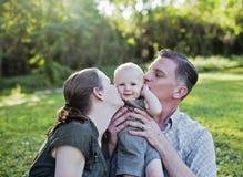 Genitori che baciano bambino Fotografia Stock Libera da Diritti