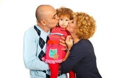 Genitori che baciano figlia sporgente le labbra Immagini Stock