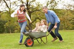 Genitori che danno a bambini giro in carriola Fotografie Stock Libere da Diritti