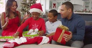 Genitori che danno a bambini i regali di Natale a casa - la ragazza apre la scatola ed elimina una renna coccola del giocattolo archivi video