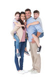 Genitori che danno sulle spalle giro ai bambini sopra fondo bianco Fotografia Stock