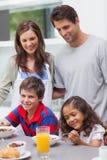 Genitori che esaminano i loro bambini che mangiano prima colazione fotografia stock