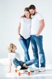 Genitori che esaminano piccola figlia sveglia che si siede sul pattino fotografia stock