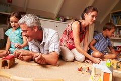Genitori che giocano con i bambini ed i giocattoli in una stanza dei giochi della soffitta Fotografie Stock Libere da Diritti