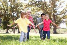 Genitori che giocano con i bambini in paese Immagini Stock Libere da Diritti