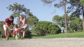 Genitori che insegnano alla figlia a guidare bici in parco archivi video