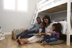 Genitori che leggono storia ai bambini nella loro camera da letto immagini stock libere da diritti
