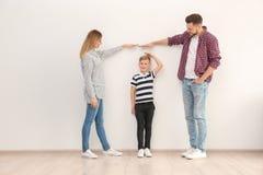 Genitori che misurano la loro altezza del ` s del figlio immagini stock
