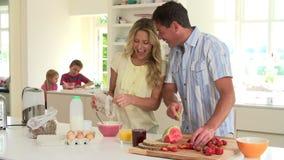 Genitori che preparano la prima colazione della famiglia in cucina video d archivio