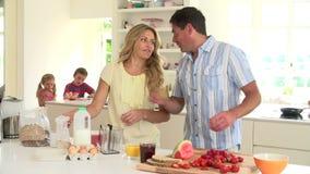 Genitori che preparano la prima colazione della famiglia in cucina stock footage