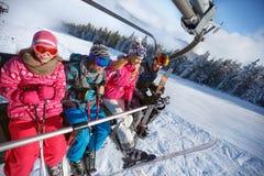 Genitori con i bambini in ascensore di sci che di sollevamento sul terreno dello sci fotografie stock libere da diritti