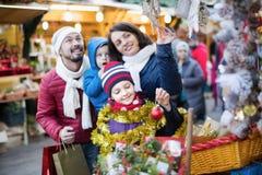Genitori con i bambini che comprano le decorazioni di feste Immagini Stock