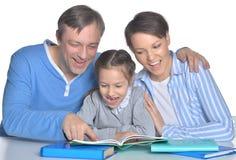 Genitori con i libri di lettura della figlia Immagine Stock