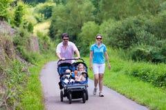 Genitori con il doppio passeggiatore Fotografie Stock Libere da Diritti
