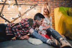 genitori con il loro bambino sui precedenti di una stella con le lampadine fotografie stock