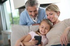 Genitori con la figlia che gioca sullo smartphone Fotografia Stock Libera da Diritti