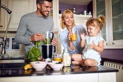 Genitori con la figlia che mangia prima colazione fotografia stock libera da diritti