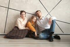 Genitori con la loro piccola figlia che si siede sul pavimento in un nuovo appartamento fotografia stock libera da diritti