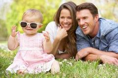 Genitori con la neonata che si siede nel campo Immagine Stock