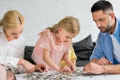 genitori con la piccola figlia sveglia che gioca con i pezzi di puzzle immagine stock