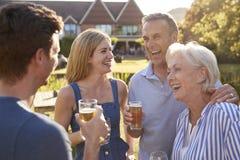 Genitori con la prole adulta che gode della bevanda all'aperto di estate al pub fotografia stock