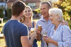 Genitori con la prole adulta che gode della bevanda all'aperto di estate al pub immagini stock libere da diritti