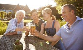 Genitori con la prole adulta che gode della bevanda all'aperto di estate al pub immagine stock libera da diritti