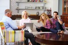 Genitori con la prole adulta facendo uso dei dispositivi di Digital a casa fotografia stock