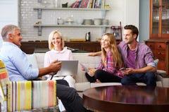Genitori con la prole adulta facendo uso dei dispositivi di Digital a casa fotografie stock libere da diritti