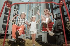 Genitori contentissimi felici che si siedono sulle oscillazioni fotografia stock