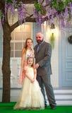 Genitori della famiglia con la figlia a casa nell'iarda di estate insieme fotografia stock