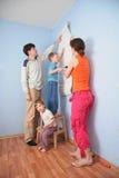 Genitori di guida del figlio per incollare le carte da parati Fotografia Stock
