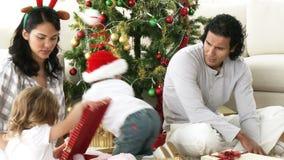 Genitori e bambini che aprono i regali di Natale a casa video d archivio