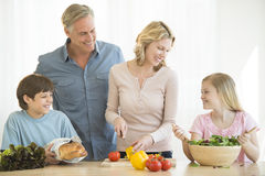 Genitori e bambini che cucinano insieme alimento al contatore Fotografia Stock