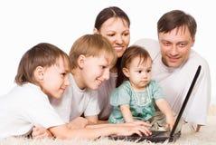 Genitori e bambini con il computer portatile Immagini Stock