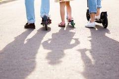 Genitori e bambino che stanno con i motorini fotografia stock