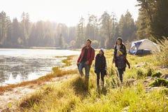 Genitori e due bambini sul viaggio di campeggio che camminano vicino ad un lago Fotografia Stock Libera da Diritti