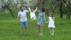 Genitori e due figlie nel giardino di fioritura della molla Colpo del movimento lento video d archivio