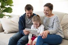 Genitori e figlia che per mezzo della compressa digitale Fotografie Stock