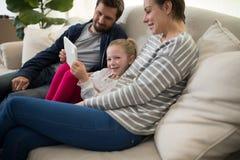 Genitori e figlia che per mezzo della compressa digitale Fotografia Stock Libera da Diritti