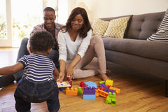 Genitori e figlio che giocano con i giocattoli sul pavimento a casa Immagini Stock Libere da Diritti